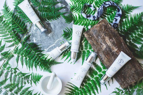 5 producten van OrganicSpa tussen plantblaadjes en een houten stronkje