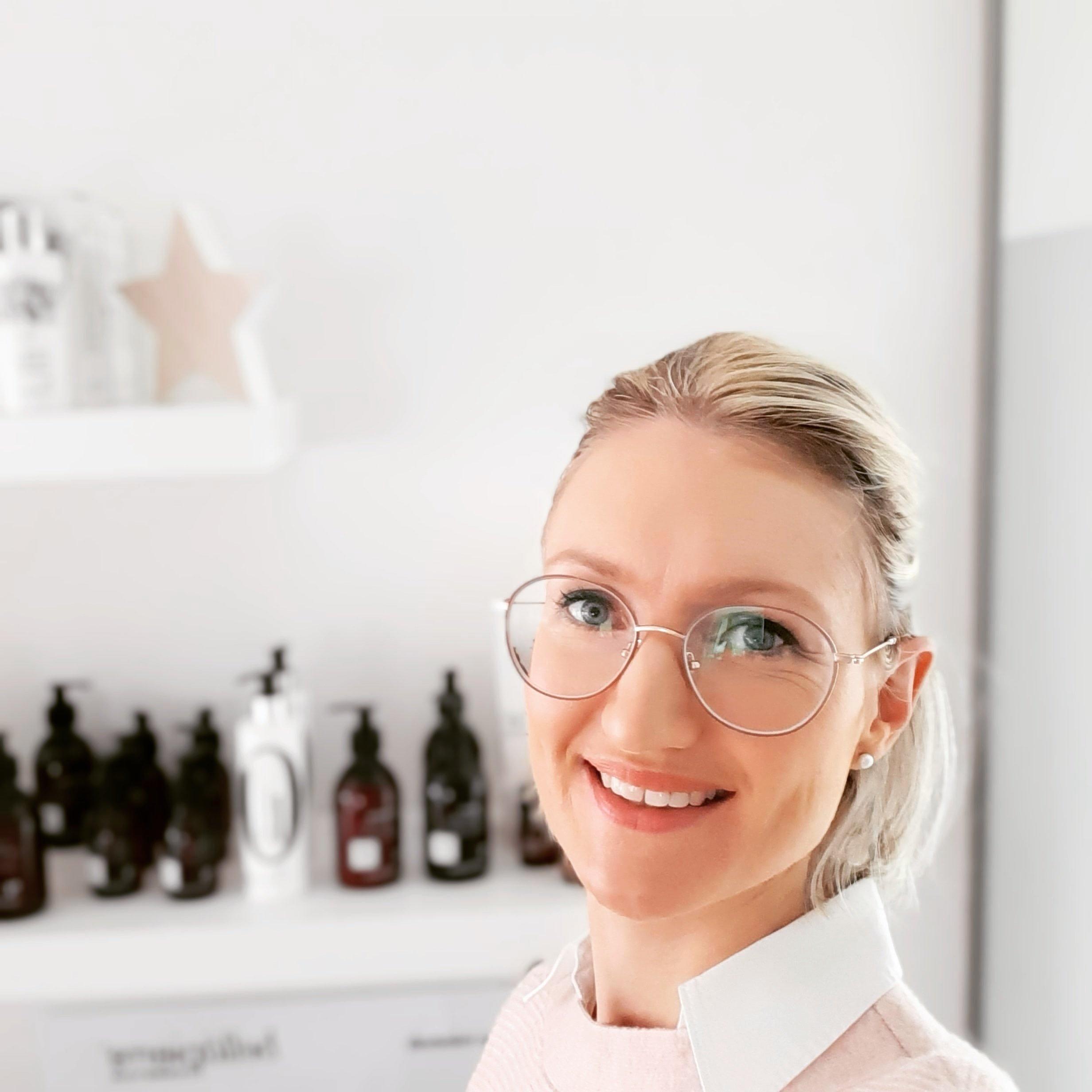 Schoonheidsspecialiste Appelterre/Ninove draagt bril en roze trui met witte blouse