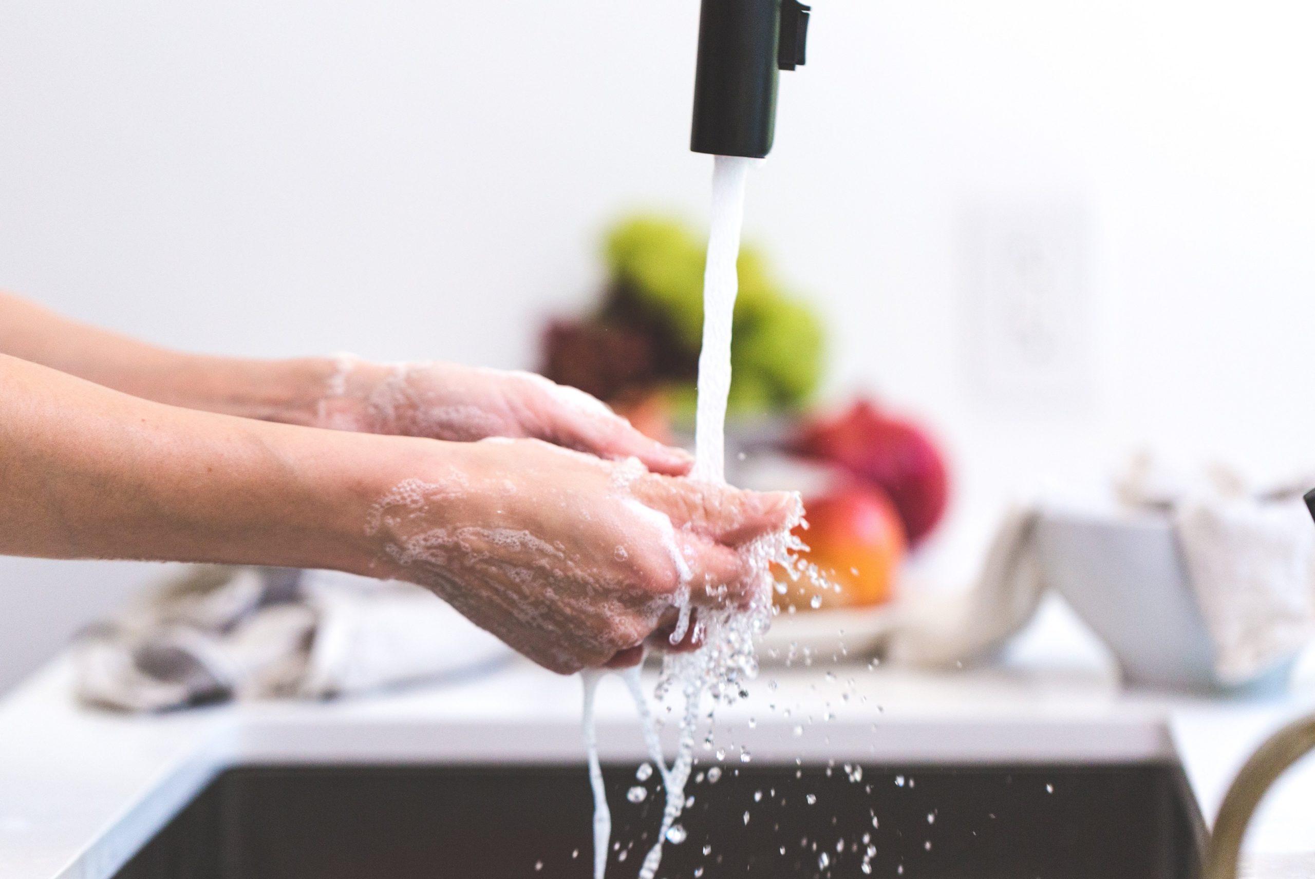 handen wassen onder stromend water met fruit op de achtergrond naast de wastafel